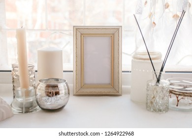 Shabby chic home design. Beautiful decoration table with a candles, dreamcacher, aroma stick and frame with copy space on the windowsill, mindfullness relax concept