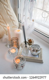 Shabby chic home design. Beautiful decoration table with a candles, dreamcacher, aroma stick on the windowsill, mindfullness relax concept