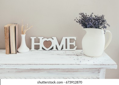 Shabby chic interior decor for farmhouse. Lavender in pitcher, books and wooden letters on a vintage shelf over pastel wall. Provence home decoration.