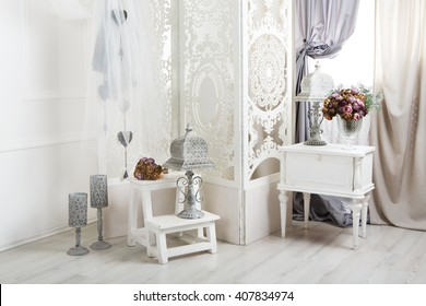 Shabby chic interior. Wedding decor, room decorated for rustic wedding, with bedside table, folding screen or room divider with white tracery and rose bouquets. High key