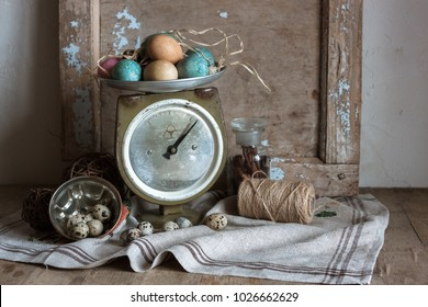 Shabby chic still life composition of scale, old wood frames, painting and quail eggs, glass bottle with cinnamon sticks, feud cloth and bast on the wooden table.The rustic country still life