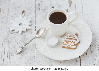 Shabby chic style coffee cup and plate with gingerbread house cookie, cinnamon sticks and other decorations for Christmas mood