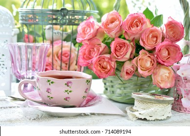 shabby chic style pink cup of tea on the table with bunch of roses and vintage bird cages in the garden