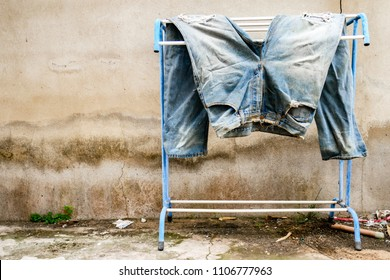 A shabby jeans was air dried  in the sun on a clothes line
