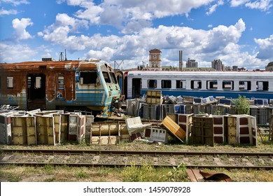 Shabby old electric train and wagons on the railway tracks in the railroad depot on the background of the sunny blue sky with white clouds. There are piles of battered seats in a front of them.