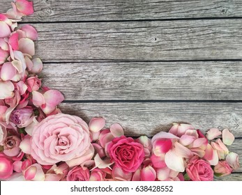 Shabby roses wallpaper. roses and petals on rustic wooden background.