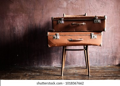 Shabby Vintage Stacked Ancient Suitcases on the chair. Travel Concept Brown Luggage Background Banner