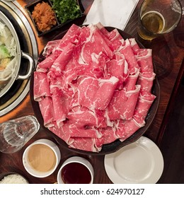 Shabu-shabu platter on table at Japanese restaurant with people eating with chopsticks