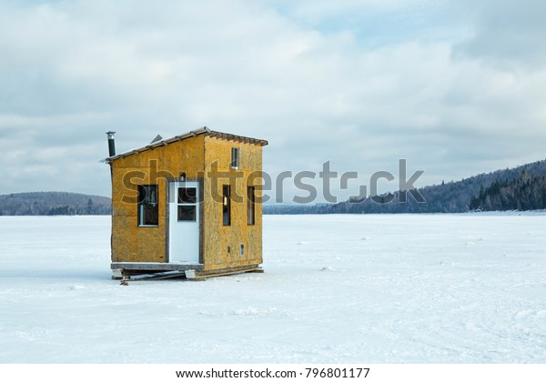 Shack made of plywood for ice fishing on a frozen lake with trees in the background