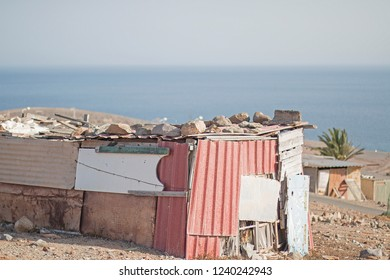 A shack on a hill. Background:  sea.