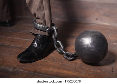 Shackles on his hand. Top view of businessman leg with shackles on it