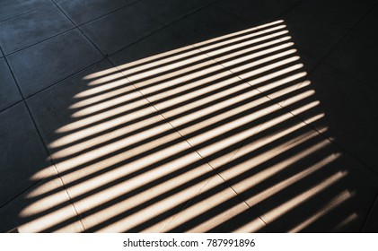 Shade and shadow on wall from a window roller shutter.