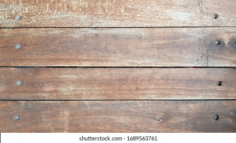 Shades of brown wood textured backdrop with scratched pattern. Old weathered wooden plank wall surface closeup. Rustic hardwood texture. Wooden background with copy space.