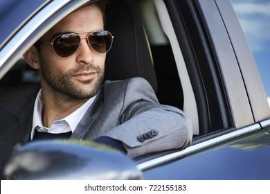 Shades dude wearing grey in car, looking away