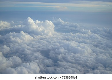 Shades of light blue color sky and constantly change floating white cloud heaven view from airplane window in the morning sunrise