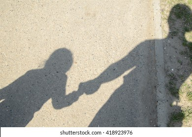 the shadow of an adult and a child