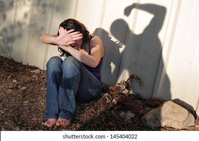 Shadow of aggressive violent man attacks and beating up an innocent woman sitting on the ground with a fist outdoors. Concept photo of physical abuse. Real people.Copy space