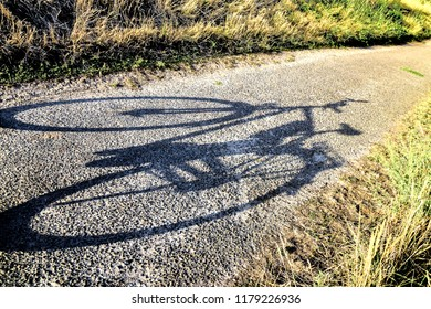 Shadow of a bicycle standing on a path.