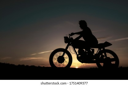 Shadow of a biker girl on a sunset background, silhouette of a girl on a bike. Black motorcycle and a woman on it.
