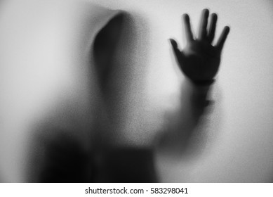 Shadow blur of horror man in jacket with hood.One hands on the glass.Dangerous man behind the frosted glass.Mystery man.Halloween background.Black and white picture.Blur picture
