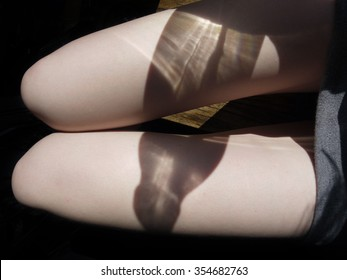 The shadow of a bottle on girl's knees as a symbol of female alcoholism