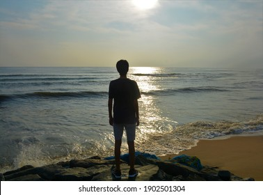 Shadow of a boy standing on a rock by the beach, and staring at the beautiful sight of the sun, the sky and the sea
