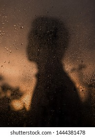 Shadow of a boy,behind a wet glass