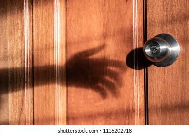 Shadow of burglar's hand trying to open the door