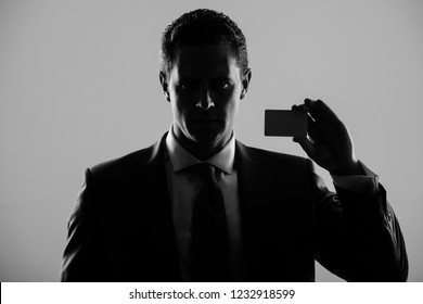 shadow business, businessman, man or manager holding bank or business card in blue formal suit and tie on grey background. banking, fraud, skimming, ecash and information