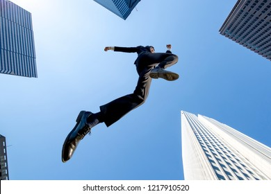 A  shadow of businessman jumping with the blue sky and skyscrapers background . Energetic · Power · Success · Challenge Image