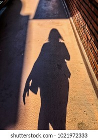 Shadow of businesswoman walking with purse and hair blowing in wind.