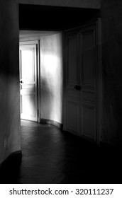 A shadow cast on a wall at the end of a dark corridor