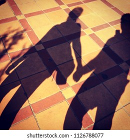 Shadow casting couple holding hands