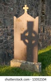 Shadow of celtic cross on gravestone in graveyard