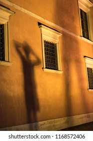 A shadow of a child standing in front of a facade