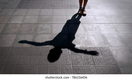 Shadow of A Child Standing on the Tiled Floor and Spreading His Arms