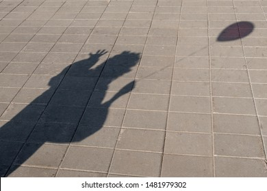Shadow from a clown with a ball in his hand. Street pavement made of stone slabs. Costume show or Halloween party. Copy space.