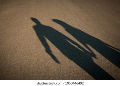 Shadow of a couple on the road holding hands. Romantic dating concept