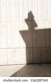 Shadow of a cross on top of a facade