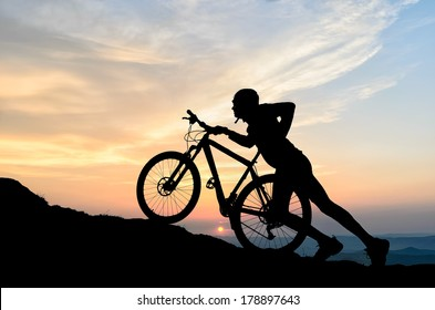 shadow of a cyclist climbing a hill while the sun is setting on the horizon