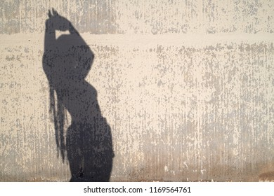 Shadow of dancing woman against concrete wall in sunshine