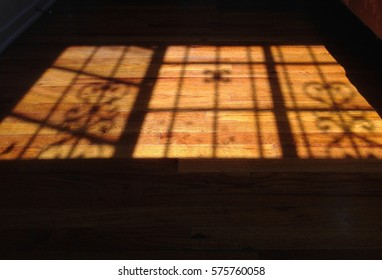 Shadow of a decorative wrought iron window protection on a wooden floor