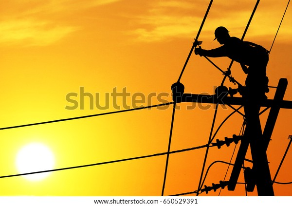 Shadow electricians repairing wire on electric power pole at the sunsetbackground blur.