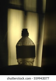 Shadow of an empty water bottle with a sports top on a structured wall