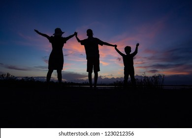 Shadow of family, mother and boy raise hands in the evening on the lake.