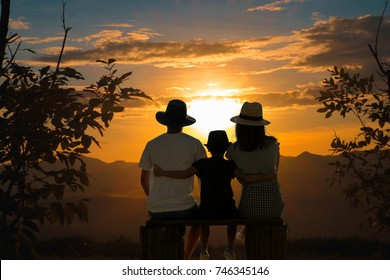 The shadow of the family traveler. Watch the sunset after the mountain in the evening. On a relaxing holiday