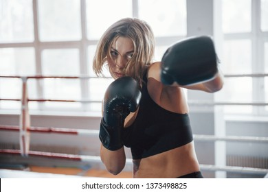 Shadow fighting. Female sportswoman training in the boxing ring. In black colored clothes.