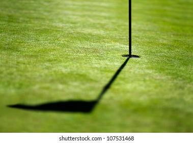 shadow of a flag on golf field