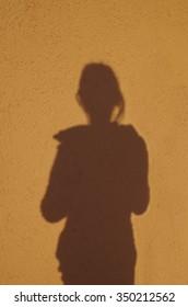Shadow girl on an orange wall