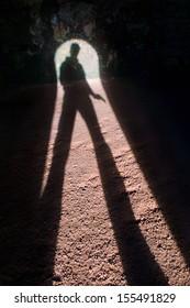 The shadow of a gunman entering a dark cellar.